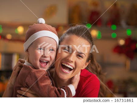 Portrait of smiling mother and baby in christmas decorated kitch 16731861