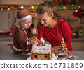 Happy mother and baby decorating christmas cookie house 16731869