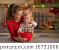Happy mother and baby whisking dough in christmas decorated kitc 16731908