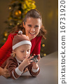 Happy mother and baby holding photo camera in front of christmas 16731920