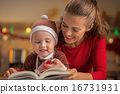 Happy mother and baby reading christmas book 16731931