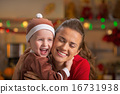Portrait of happy mother and baby hugging in christmas decorated 16731938
