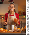 Happy young housewife preparing orange jam in christmas decorate 16731990
