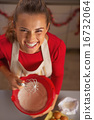 Portrait of smiling young housewife dough whisk 16732064