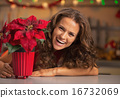 Smiling young woman looking out from christmas rose in christmas 16732069