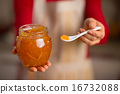 Closeup on young housewife giving spoon of orange jam 16732088