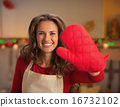 Happy young housewife showing red kitchen glove 16732102