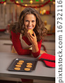 Happy young housewife eating christmas cookie in kitchen 16732116