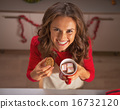 Portrait of smiling young woman enjoying christmas cookies in ki 16732120