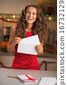 Happy young housewife in red dress putting christmas letter into 16732129