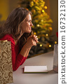 Thoughtful young woman making christmas list of presents 16732130