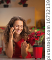 Smiling young housewife talking phone and playing with christmas 16732139