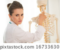 Portrait of medical doctor woman showing spine on human skeleton 16733630
