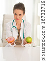 Medical doctor woman giving a choice between apple and donut 16733719
