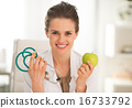 Happy medical doctor woman showing apple and stethoscope 16733792