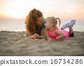 Happy mother and baby girl laying on beach in the evening 16734286