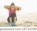 Healthy young woman doing abdominal crunch on beach 16734296