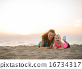 Healthy mother and baby girl laying on beach in the evening 16734317