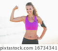 Portrait of smiling fitness young woman on beach showing biceps 16734341
