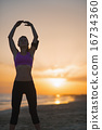 Silhouette of fitness young woman stretching on beach at dusk 16734360