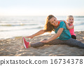 Healthy mother and baby girl stretching on beach in the evening 16734378