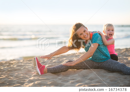 Stock Photo: Healthy mother and baby girl stretching on beach in the evening