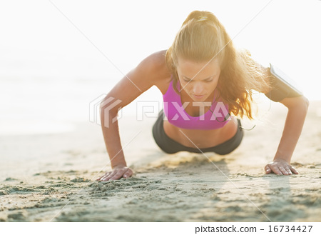 Fitness young woman doing push ups on beach 16734427