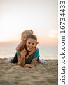 Happy mother and baby girl laying on beach in the evening 16734433