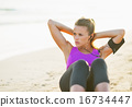 Fitness young woman doing abdominal crunch on beach 16734447