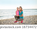 Portrait of healthy mother and baby girl on beach in the evening 16734472