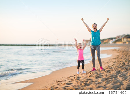 Healthy mother and baby girl rejoicing in the evening on beach 16734492