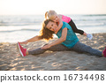Healthy mother and baby girl stretching on beach in the evening 16734498