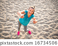 Happy fitness young woman on beach showing thumbs up 16734506