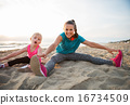 Healthy mother and baby girl stretching on beach in the evening 16734509