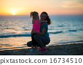Silhouette of mother and baby girl hugging on beach 16734510