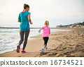 Healthy mother and baby girl running on beach. rear view 16734521