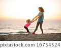 Mother and baby girl having fun time on beach in the evening 16734524