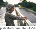 Portrait of fitness young woman in rainy city 16734556