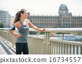 Portrait of fitness young woman in the city looking into distanc 16734557