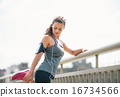 Portrait of fitness young woman stretching outdoors 16734566
