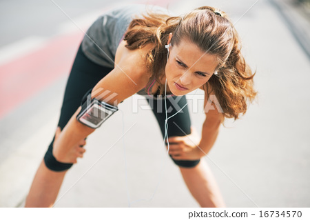 Portrait of tired fitness young woman outdoors in the city catch 16734570