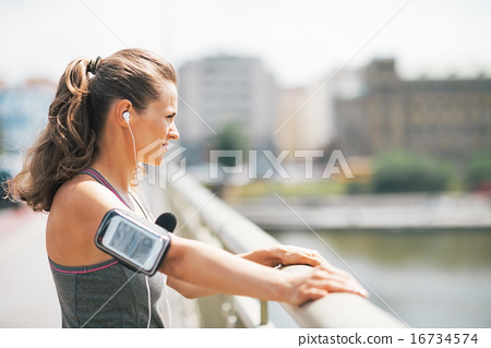 Fitness young woman in the city looking into distance 16734574