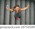 Portrait of happy fitness young woman with cell phone outdoors i 16734589