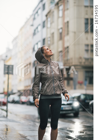 Fitness young woman exposed to rain while jogging outdoors in th 16734595