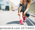 Closeup on fitness young woman tying shoelaces in the city 16734602