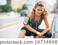 Portrait of tired fitness young woman outdoors in the city 16734608