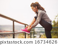 Fitness young woman tying shoelaces outdoors 16734626