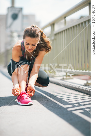 Fitness young woman tying shoelaces in the city 16734637