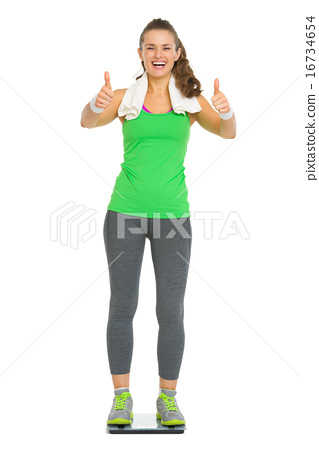 Happy fitness young woman standing on scales and showing thumbs 16734654