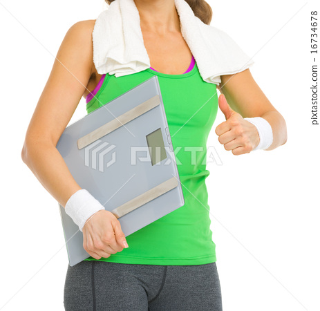 Closeup on fitness woman with scales showing thumbs up 16734678